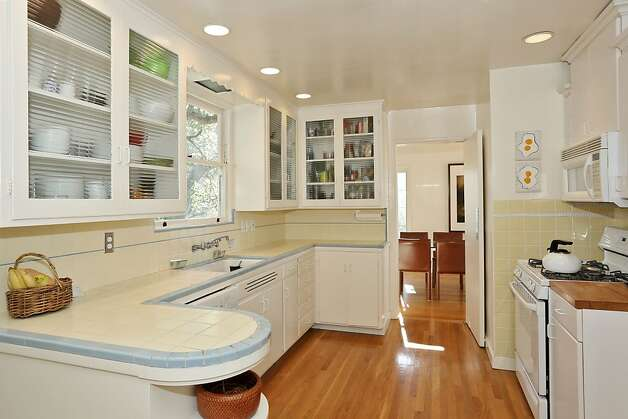 The kitchen on the top level has hardwood floors and tile countertops. Photo: Liz Rusby