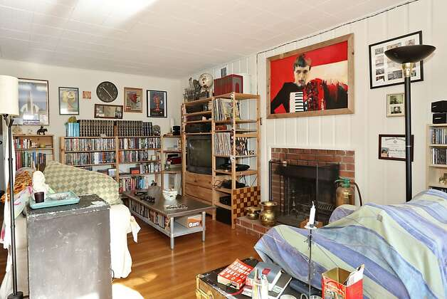 The living room in the middle level has a fireplace with a brick surround. Photo: Liz Rusby