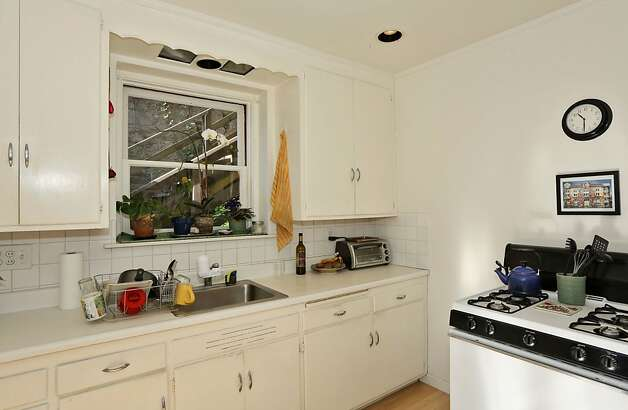 The lower-level unit's kitchen has hardwood floors and tile backsplashes. Photo: Liz Rusby
