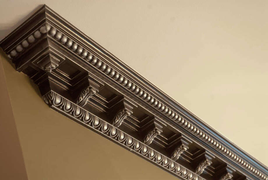 This crown molding was painted a shimmery black, references the banisters and the bookshelves.
