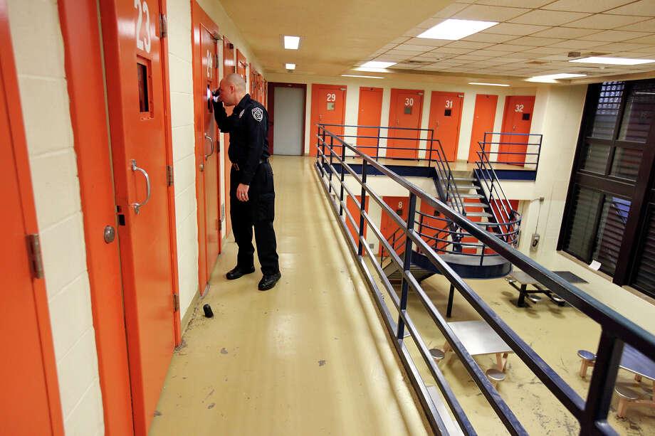 Deputy Steven Colon checks on inmates at the Bexar County Jail. Photo: Edward A. Ornelas, San Antonio Express-News / © 2013 San Antonio Express-News