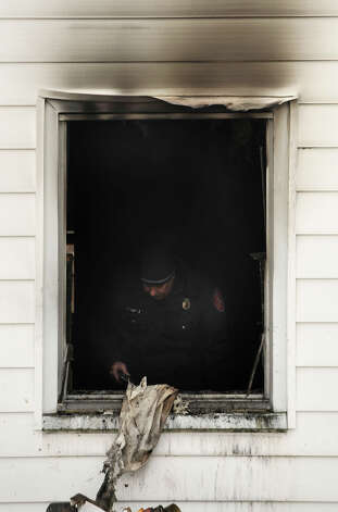 Firefighters investigate the scene after they were called to a house fire at 6 Dogwood Drive in Danbury on Friday, Jan. 25, 2013. Photo: Jason Rearick / The News-Times