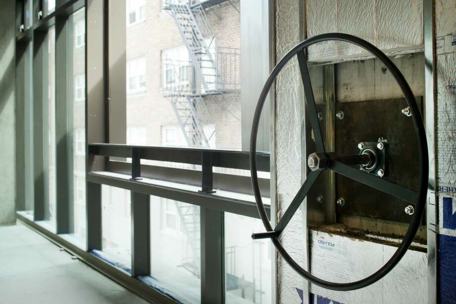 Users can open the door and window by turning hand wheels that connect pivot bolts on the exterior of the building via threaded rods. Unit 600, a 2,237-square-foot shell, is listed for $1.175 million. Photo: Courtesy A. Carol McDaniel/Windermere Real Estate