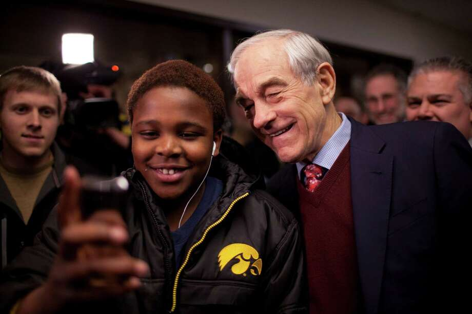 Republican presidential candidate Ron Paul poses for a photo with a boy at Coon Rapids Middle School in Coon Rapids, Minn., Tuesday, Feb. 7, 2012. Photo: Jeff Wheeler, Associated Press / The Star Tribune