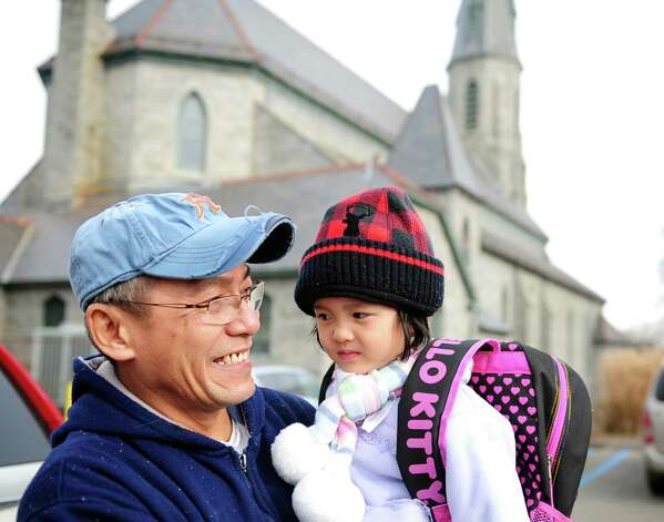 Phung Huynh, a long time member of St. Augustine Parish, where Monsignor Kevin Wallin was formerly a pastor, talks about the disgraced priest's legal troubles Friday, Jan. 25, 2013 outside St. Augustine School where his daughter, Truc, 3, attends preschool. Photo: Autumn Driscoll / Connecticut Post