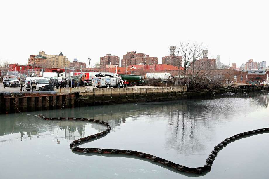 NEW YORK, NY - JANUARY 25:  Officials stand on the side of the Gowanus Canal as a common dolphin comes up for air after getting stuck on January 25, 2013 in Brooklyn borough of New York City. Officials are waiting till high tide in the hopes that the stuck dolphin will be able to free itself from the canal. Photo: Michael Heiman, Getty Images / 2013 Getty Images