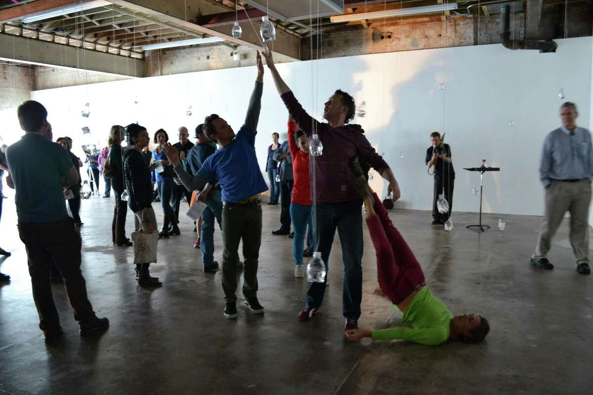 """Dancers Spencer Gavin Herring, from left, jhon stronks and Leslie Scates perform in the center of artist Tony Feher's installation """"Free Fall"""" during the opening weekend of the exhibit, which features a series of live performances. Trombonist David Dove is in the background."""