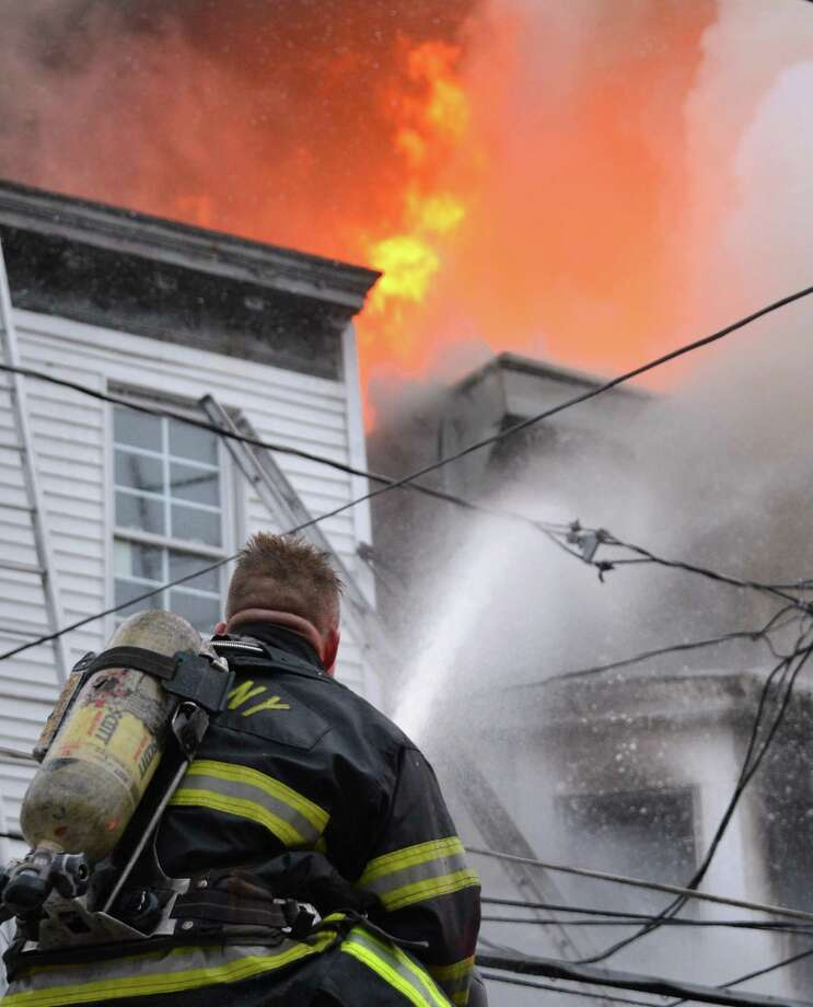 An Albany firefighter pours water into a fiery blaze 159 Dove Street in Albany Friday Jan. 25, 2013.  (John Carl D'Annibale / Times Union) Photo: John Carl D'Annibale