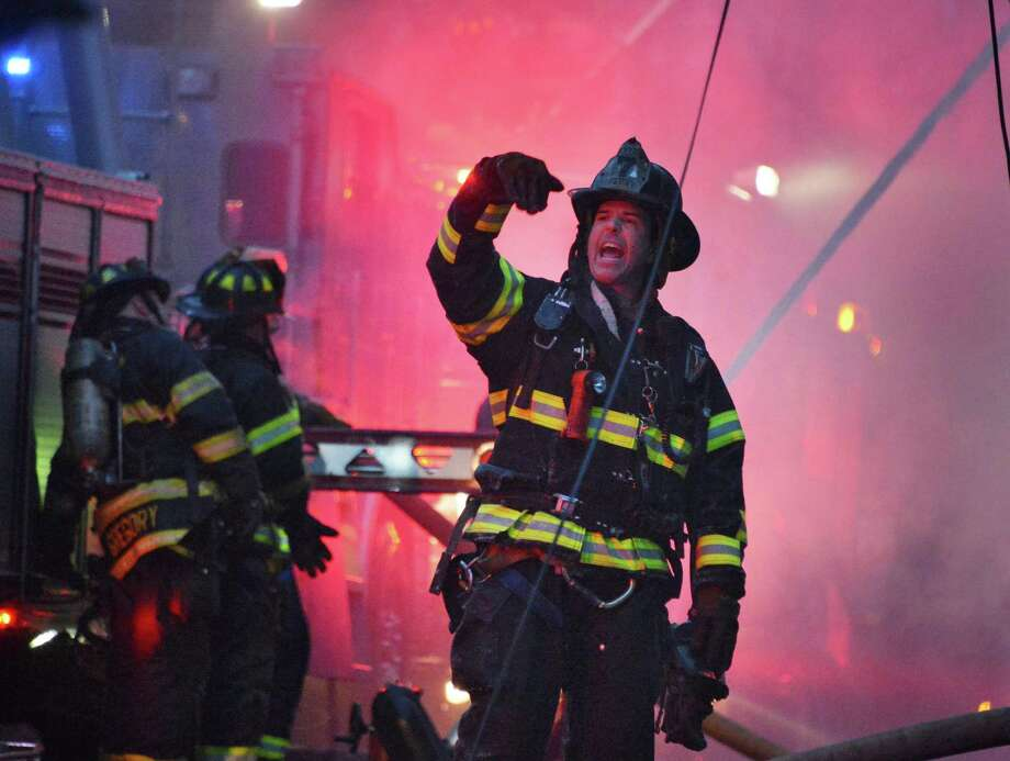 An Albany firefighter calls out orders as they battle a blaze at 159 Dove Street in Albany Friday Jan. 25, 2013.  (John Carl D'Annibale / Times Union) Photo: John Carl D'Annibale