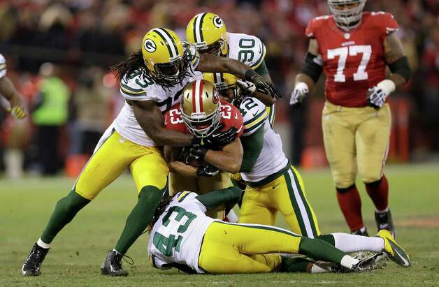 San Francisco 49ers running back LaMichael James (23) is tackled by Green Bay Packers outside linebacker Erik Walden (93), strong safety Morgan Burnett (42), nose tackle B.J. Raji (90) and free safety M.D. Jennings during the second quarter of an NFC divisional playoff NFL football game in San Francisco, Saturday, Jan. 12, 2013. (AP Photo/Marcio Jose Sanchez) Photo: Marcio Jose Sanchez, Associated Press / AP