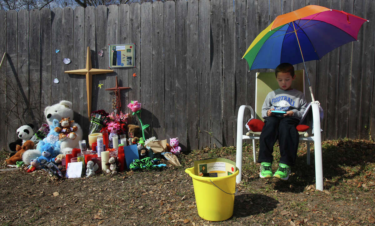 Boston Olguin,4, plays a game Friday January 25, 2013 while sitting next to an impromptu memorial set up on the 9300 block of Autumn Sunrise in honor of six-year-old Brandon Douglas Abrams. Abrams was on his bike on a sidewalk Thursday evening when a 17-year-old male driving a Ford Ranger struck and killed the boy.
