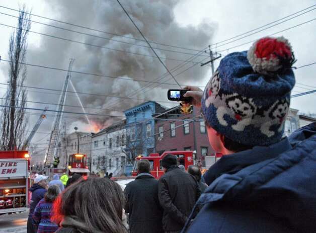 Onlookers use their smart phones to record a multi building fire on Dove Street in Albany Friday Jan. 25, 2013.  (John Carl D'Annibale / Times Union) Photo: John Carl D'Annibale
