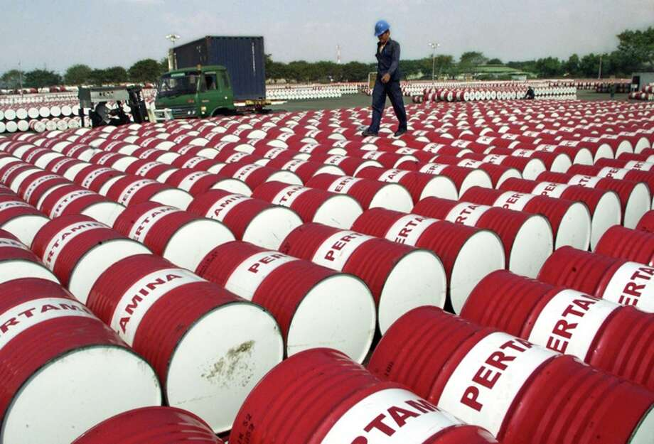 An Indonesian worker walks on barrels of oil at a distribution station of the state-owned oil company Pertamina in Jakarta, Indonesia, Friday, June 24, 2005. Photo: TATAN SYUFLANA, ASSOCIATED PRESS / AP2005