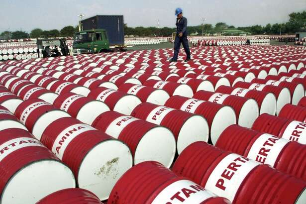 An Indonesian worker walks on barrels of oil at a distribution station of the state-owned oil company Pertamina in Jakarta, Indonesia, Friday, June 24, 2005. Crude oil futures briefly touched US$60 a barrel in Asian trading Friday, hours after reaching the psychologically important mark in New York, as prices rose on speculative buying and fears of supply disruptions due to refinery glitches. (AP Photo/Tatan Syuflana)