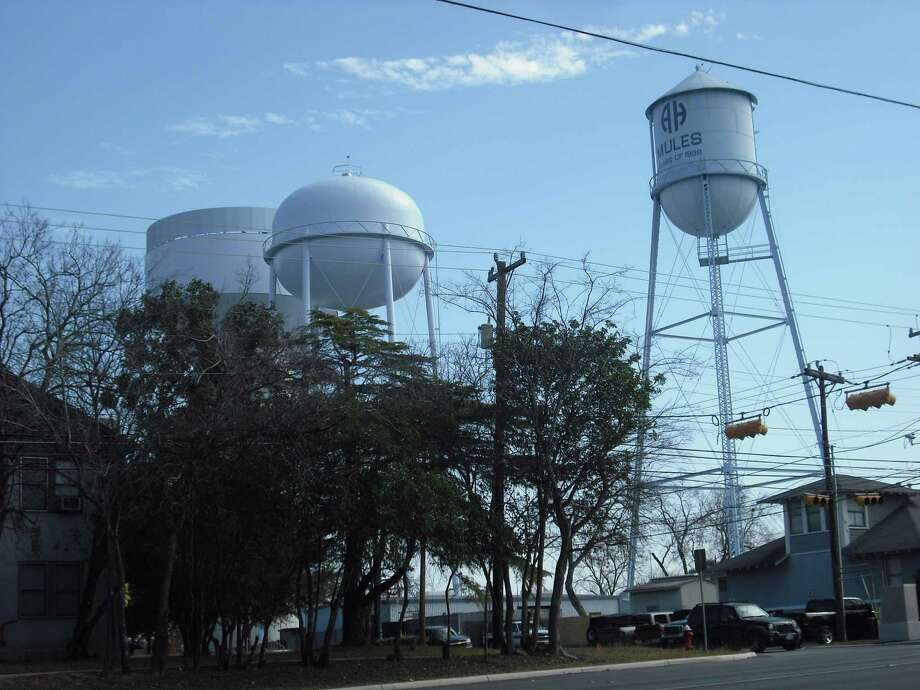 Contractors will spend Monday taking down, piece by piece, Alamo Heights water tower - nicknamed by residents the tin man (right). The structure dates back to 1928. Photo: Edmond Ortiz / For North Central