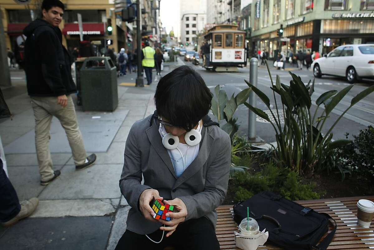 Waiting his next two minute challenge, Francisco Perez, 18, quietly twists his Rubik's Cube on Powell Street in San Francisco.