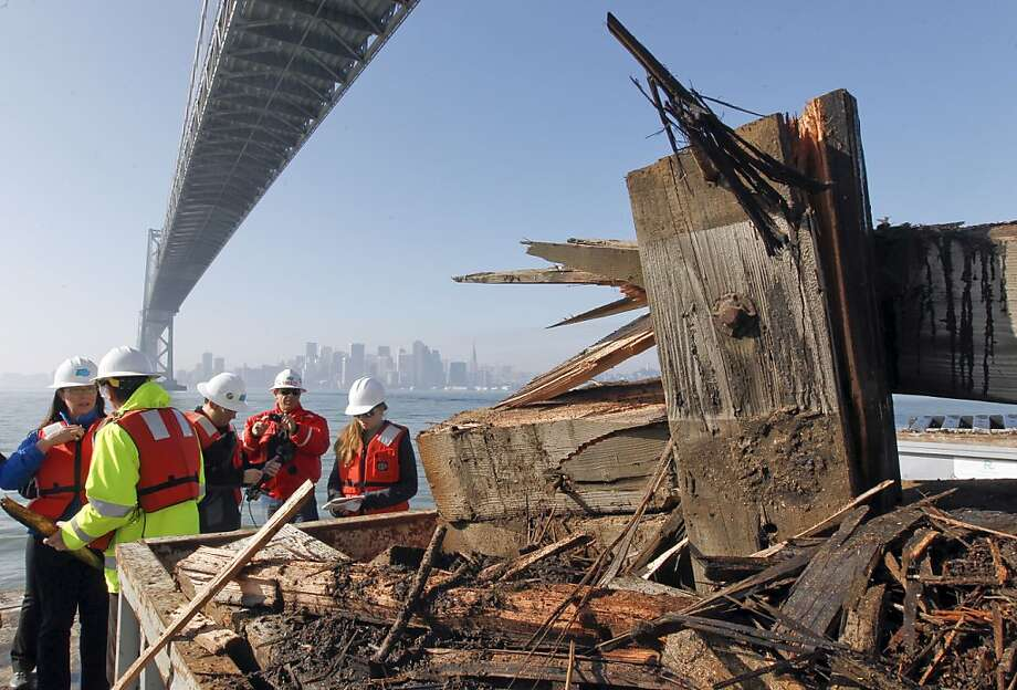 Debris is collected from the damaged bumper at the bottom of the suspension tower of the Bay Bridge. Photo: Michael Macor, The Chronicle