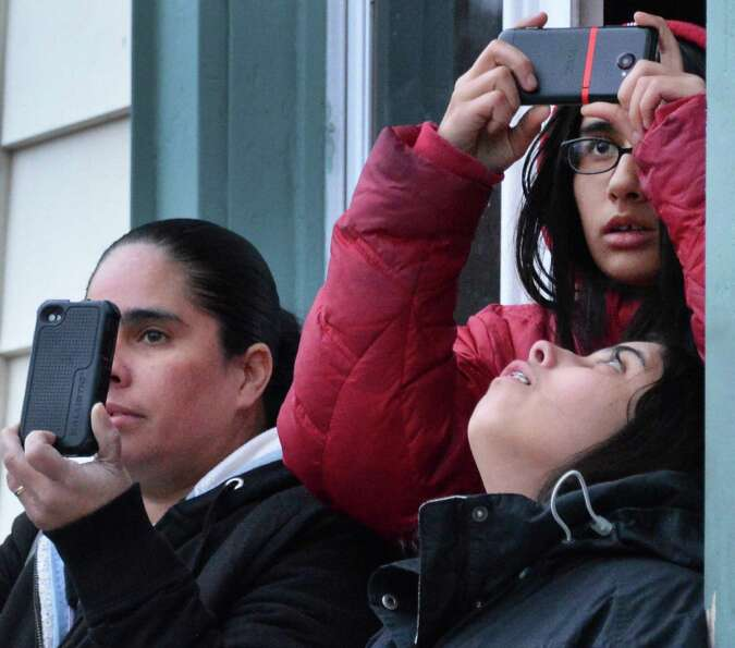 Onlookers use their smart phones to record a multi building fire on Dove Street in Albany Friday Jan