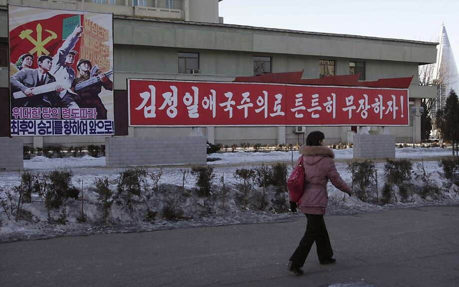 "A woman walks by a board which reads ""Forward to Final Victory under Leadership of Great Party,? left, and another reads reads ""Let's firmly arm ourselves with the patriotism of Kim Jong Il,"" in Changgwang Street, Pothonggang District of Pyongyang, North Korea, Friday Jan, 25, 2013. Following new U.N. sanctions punishing North Korea for a December rocket launch, North Korea warned that it would continue launching long-range rockets and conduct a nuclear test. (AP Photo/Kim Kwang Hyon) Photo: Kim Kwang Hyon, Associated Press"