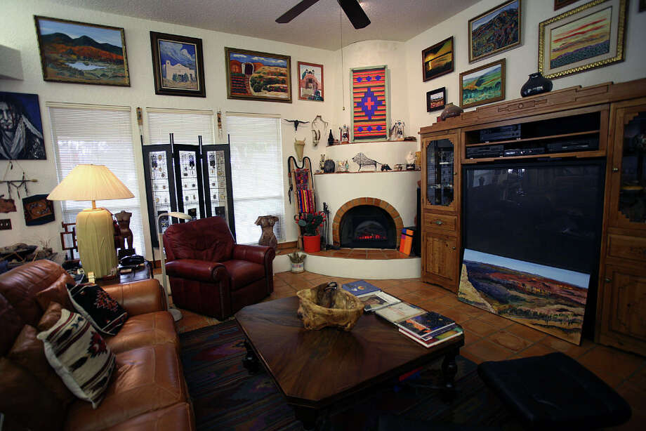 The Cardenases had a Santa Fe-style fireplace built in their Hollywood Park home. Its two ledges display Native American art; one of HenryÕs landscapes sits below the television; Southwest paintings cover the walls. Photo: Danny Warner
