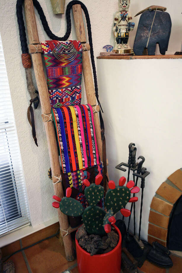 A ladder by the Santa Fe-style fireplace displays Native American weavings. Photo: Danny Warner