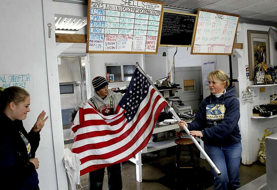 With a break in the rain, farm manager Ginny Lunny-Cummings, (right) gets help from her niece Brigid Lunny and nephew Sean Lunny re-hanging their U.S. flag outside their retail shop in Point Reyes, Calif. on Saturday Dec. 1, 2012. Photo: Michael Macor, The Chronicle