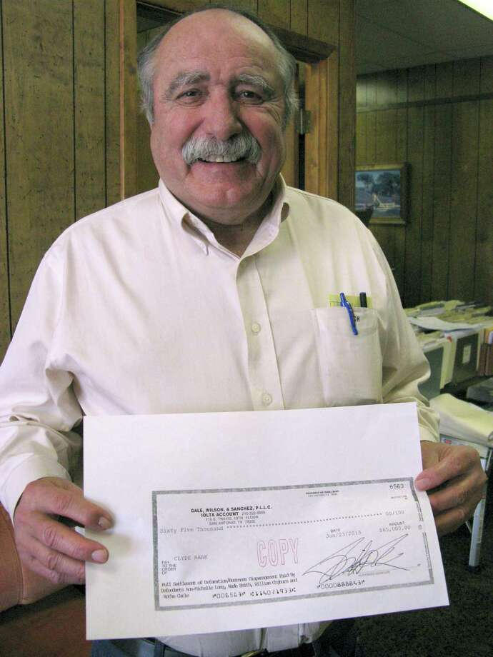 Former Hondo City Councilman Clyde Haak shows off an enlargement of the $65,000 check he received Thursday as settlement of a defamation lawsuit he filed against Hondo Councilwoman Ann-Michelle Long and three other people involved in running a 2011 newspaper ad that Haak says made false claims about him. Photo: Zeke MacCormack, San Antonio Express-News / San Antonio Express-News
