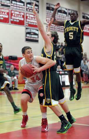 New Canaan's Zachary Allen looks to pass as he is defended by Trinity Catholic's Dan O'Leary during Friday's boys basketball game at New Canaan High School on January 25, 2013. Photo: Lindsay Perry / Stamford Advocate