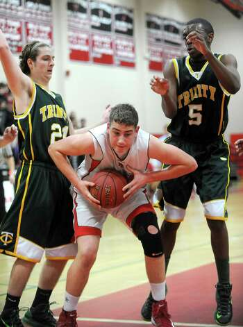 New Canaan's Zachary Allen pulls down a rebound during Friday's boys basketball gameagainst Trinity Catholic at New Canaan High School on January 25, 2013. Photo: Lindsay Perry / Stamford Advocate