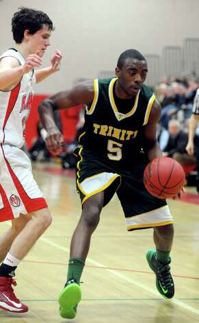 Trinity Catholic's Brandon Wheeler controls the ball during Friday's boys basketball game at New Canaan High School on January 25, 2013. Photo: Lindsay Perry / Stamford Advocate
