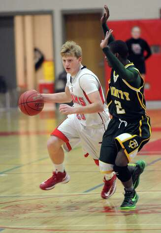 New Canaan's Andrew Read controls the ball as he is guarded by Trinity Catholic's Shadrac Casimir during Friday's boys basketball game at New Canaan High School on January 25, 2013. Photo: Lindsay Perry / Stamford Advocate