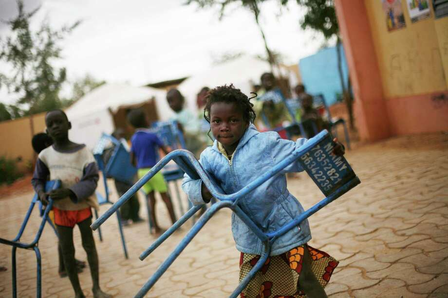 An internally displaced child carries a chair in the IDP camp sent ouside Sevare, some 620 kms (400 miles)  north of Mali's capital  Bamako Friday, Jan. 25, 2013.  One wing of Mali's Ansar Dine rebel group has split off to create its own movement, saying that they want to negotiate a solution to the crisis in Mali, in a declaration that indicates at least some of the members of the al-Qaida-linked group are searching for a way out of the extremist movement in the wake of French airstrikes. (AP Photo/Jerome Delay) Photo: Jerome Delay