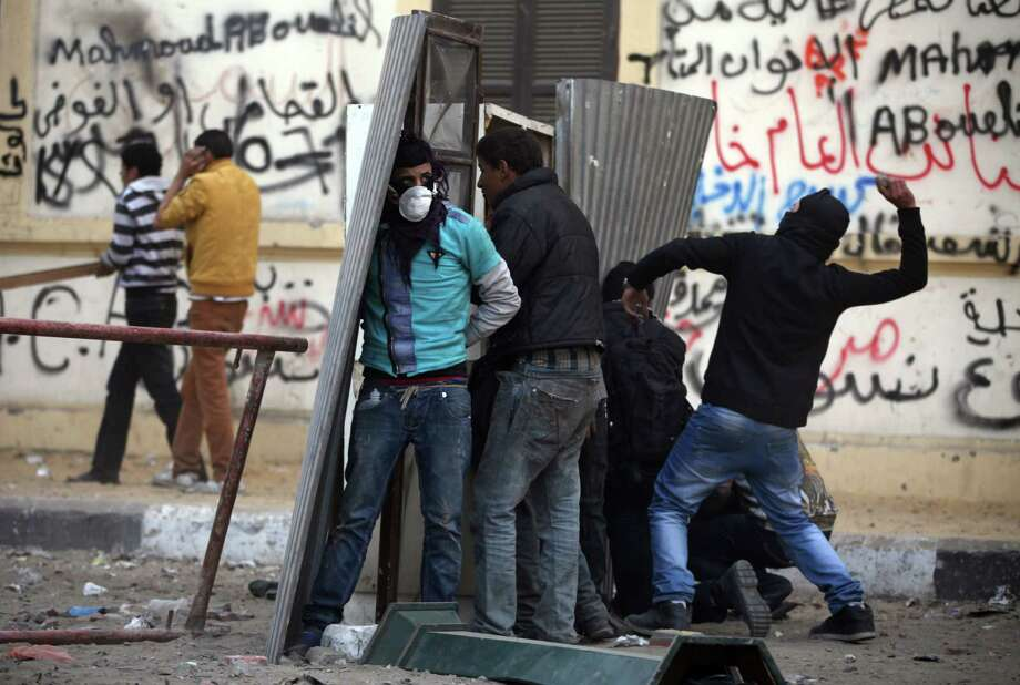 Egyptian protesters take cover as they clash with riot police, not seen, near Tahrir Square, Cairo, Egypt, Friday, Jan. 25, 2013. Two years after Egypt's revolution began, the country's schism was on display Friday as the mainly liberal and secular opposition held rallies saying the goals of the pro-democracy uprising have not been met and denouncing Islamist President Mohammed Morsi. With the anniversary, Egypt is definitively in the new phase of its upheaval. (AP Photo/Khalil Hamra) Photo: Khalil Hamra