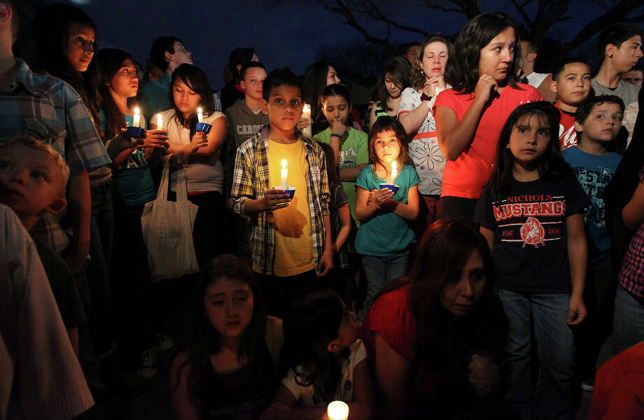 Over 100 mourners pay respects to seven-year-old Brandon Abrams during a vigil on the Northwest Side of the city on Friday, Jan. 25, 2013. The vigil was for the young boy who was killed after a driver of a truck collided with Abrams' bicycle in a neighborhood on Autumn Sunrise road. Stuffed toys, pictures and written words of condolences were tacked to a fence while candles flickered around a memorial.  Around 6:30 p.m. mourners, young and old, converged on the site. Friends and family members spoke fondly of the boy who most said loved to smile. Cub Scout Pack 352 - which Abrams belonged - came out as a unit and lit candles in memory of their fallen comrade. Donations were dropped in a bucket beside the memorial to help the family defer the cost of putting their child to rest. Photo: Kin Man Hui, San Antonio Express-News / © 2012 San Antonio Express-News