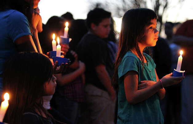 Haylee Salas, 7, holds a candle while joining over 100 mourners to pay respects to six-year-old Brandon Abrams during a vigil on the Northwest Side of the city on Friday, Jan. 25, 2013. Photo: Kin Man Hui, San Antonio Express-News / © 2012 San Antonio Express-News