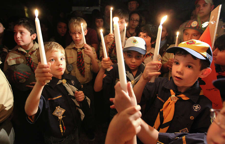 Cub Scout Pack 352 light candles in memory of their fallen friend and fellow cub scout, Brandon Abrams, during a vigil attended by over 100 mourners on the Northwest Side of the city on Friday, Jan. 25, 2013. The vigil was for the young boy who was killed after a driver of a truck collided with Abrams' bicycle in a neighborhood on Autumn Sunrise road. Stuffed toys, pictures and written words of condolences were tacked to a fence while candles flickered around a memorial.  Around 6:30 p.m. mourners, young and old, converged on the site. Friends and family members spoke fondly of the boy who most said loved to smile. Cub Scout Pack 352 - which Abrams belonged - came out as a unit and lit candles in memory of their fallen comrade. Donations were dropped in a bucket beside the memorial to help the family defer the cost of putting their child to rest. Photo: Kin Man Hui, San Antonio Express-News / © 2012 San Antonio Express-News
