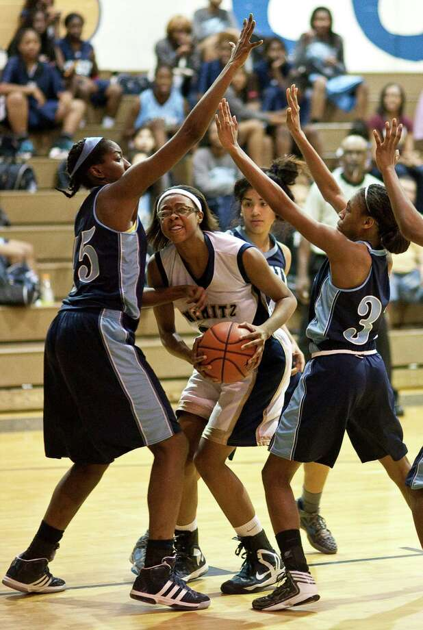 Nimitz High School's Briane Harrison, center, has trouble putting up a shot as she's swarmed by a host of Elsik High School players during the second half of a high school basketball game, Friday, Jan. 25, at Nimitz High School in Houston. Photo: Nick De La Torre, Houston Chronicle / © 2013  Houston Chronicle
