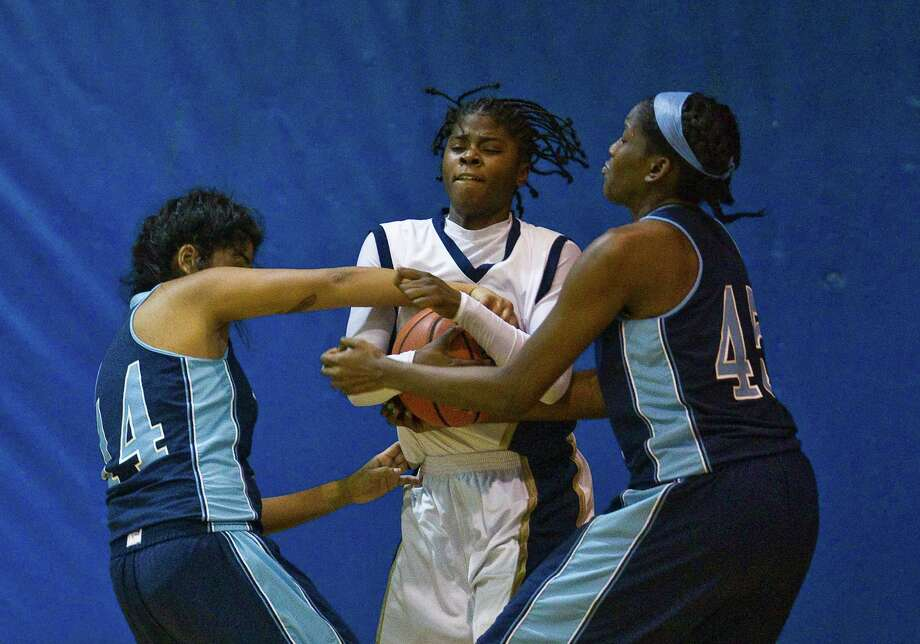 Nimitz High School's Tiara Riley, center, tries to protect the ball from Elsik High School's Gabby Ocamas, left, and Jane Babammel during the first half of a high school basketball game, Friday, Jan. 25, at Nimitz High School in Houston. Photo: Nick De La Torre, Houston Chronicle / © 2013  Houston Chronicle