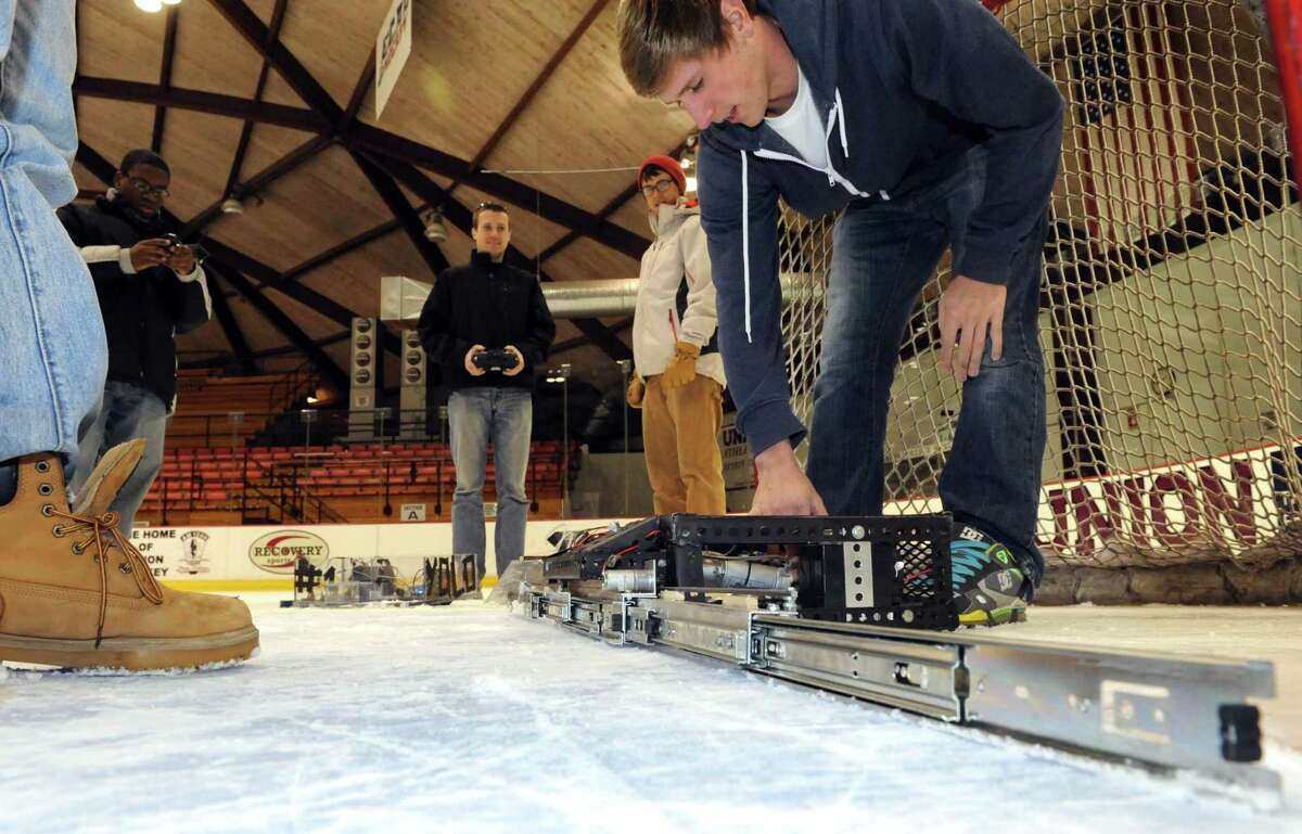 Mechanical engineering student Matt Wahl, right, adjusts a defensive goaltending robot at Union College on Friday Jan. 25,2013 in Schenectady, N.Y. (Michael P. Farrell/Times Union)