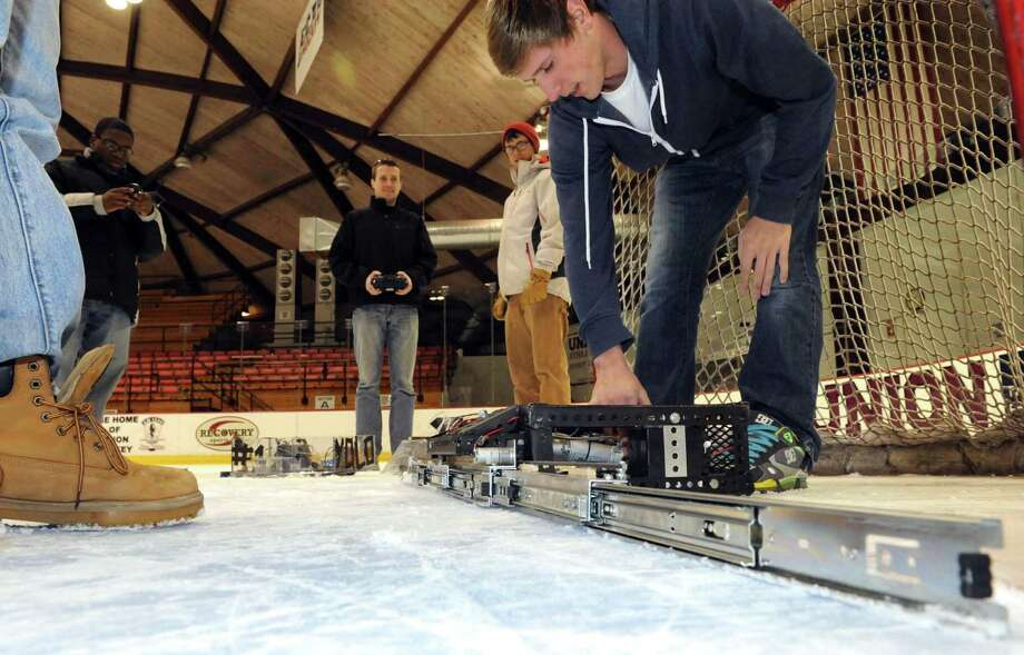 Mechanical engineering student Matt Wahl, right, adjusts a defensive goaltending robot at Union College on Friday Jan. 25,2013 in Schenectady, N.Y. (Michael P. Farrell/Times Union) Photo: Michael P. Farrell