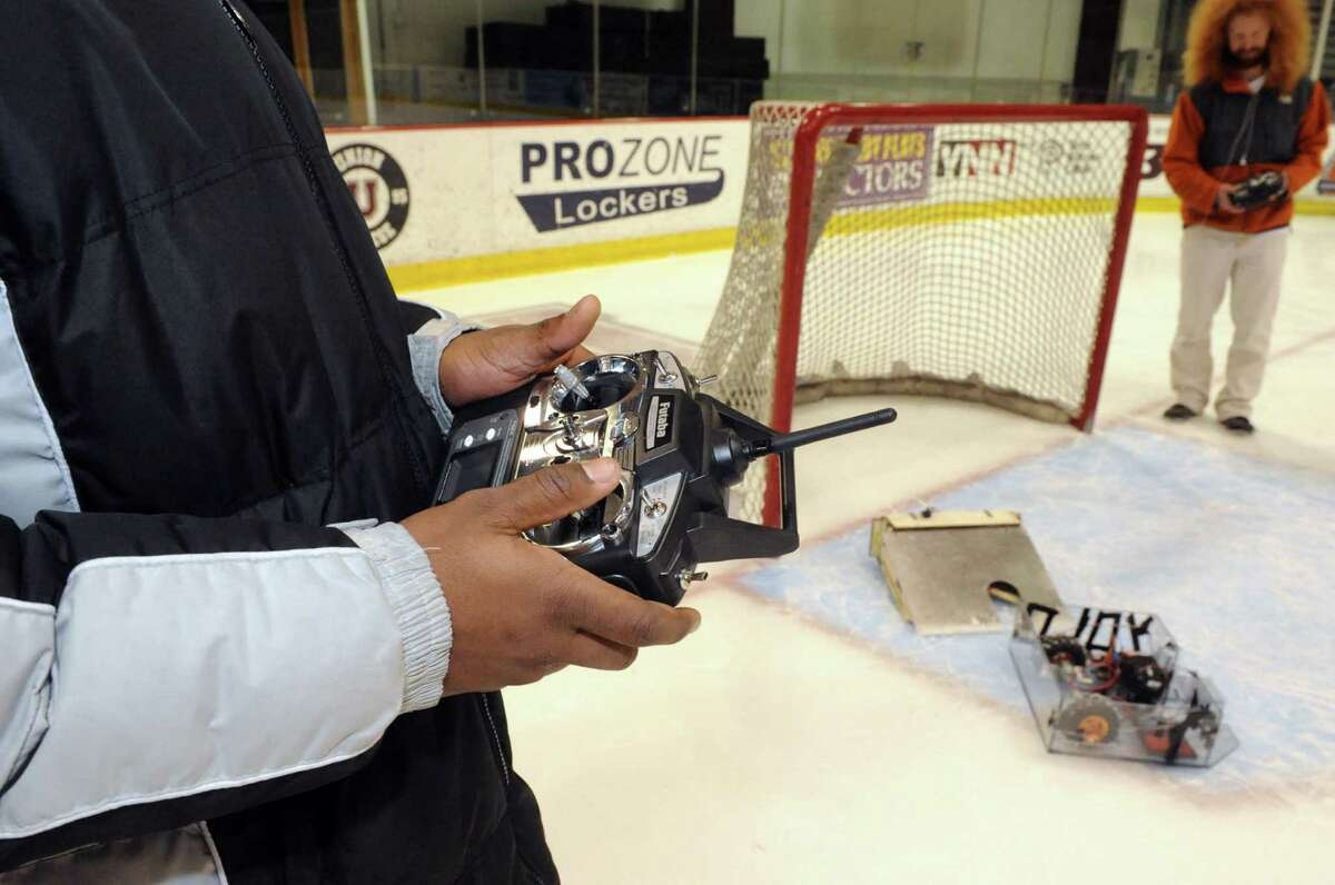 Mechanical engineering student Bessena Cabe, left, controls his offensive hockey robot at Union College on Friday Jan. 25,2013 in Schenectady, N.Y. (Michael P. Farrell/Times Union)