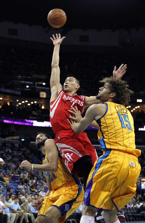 Rockets point guard Jeremy Lin drives to the basket as Robin Lopez and Greivis Vasquez of the Hornets defend. Photo: Gerald Herbert