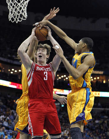 Rockets center Omer Asik attempts a shot while Anthony Davis and Robin Lopez of the Hornets defend. Photo: Gerald Herbert