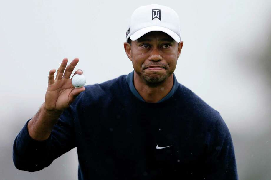 Tiger Woods picks up his ball after finishing his round on the north course at Torrey Pines Golf Course during the second round of the Farmers Insurance Open golf tournament Friday, Jan. 25, 2013, in San Diego. (AP Photo/Gregory Bull) Photo: Gregory Bull