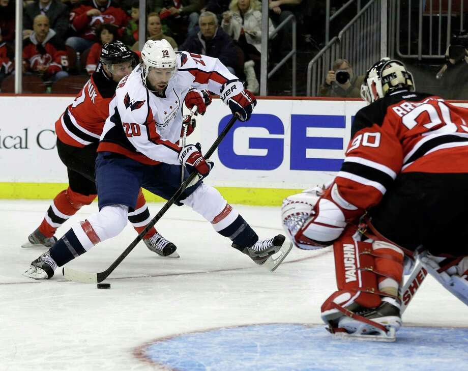 Washington Capitals' Troy Brouwer (20) takes a shot on New Jersey Devils goalie Martin Brodeur during the first period of an NHL hockey game Friday, Jan. 25, 2013, in Newark, N.J. (AP Photo/Mel Evans) Photo: Mel Evans
