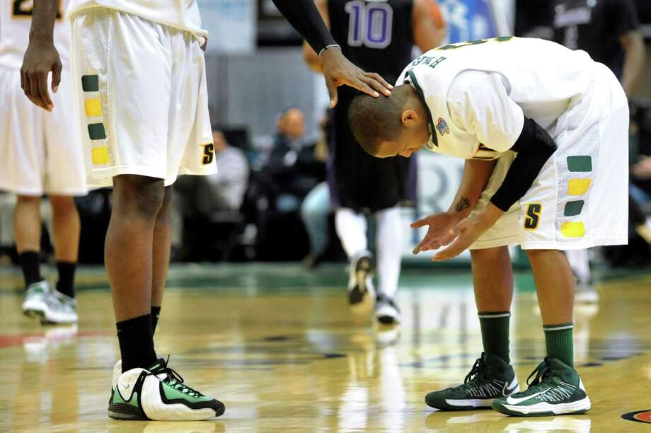 Siena's Evan Hymes, right, reacts to his foul in the final seconds of their basketball game against Niagara on Friday, Jan. 25, 2013, at Times Union Center in Albany, N.Y. Teammate O.D. Anosike offers a consoling hand. Niagara wins 78-69. (Cindy Schultz / Times Union) Photo: Cindy Schultz / 00020763A