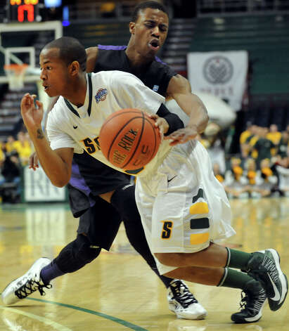 Siena's Evan Hymes (5), center, drives past Niagara's Tahjere McCall (5) during their basketball game on Friday, Jan. 25, 2013, at Times Union Center in Albany, N.Y. (Cindy Schultz / Times Union) Photo: Cindy Schultz / 00020763A