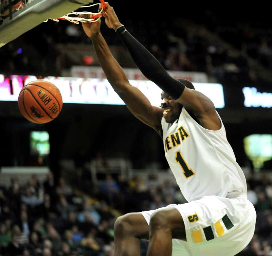 Siena's O.D. Anosike (1) hangs onto the rim as he dunks the ball during their basketball game against Niagara on Friday, Jan. 25, 2013, at Times Union Center in Albany, N.Y. (Cindy Schultz / Times Union) Photo: Cindy Schultz / 00020763A