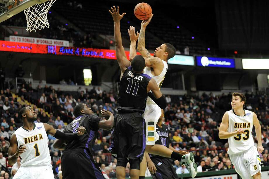 Siena's Davis Martens (21), center, goes to the hoop as Niagara's Ameen Tanksley (11) defends during their basketball game on Friday, Jan. 25, 2013, at Times Union Center in Albany, N.Y. (Cindy Schultz / Times Union) Photo: Cindy Schultz / 00020763A