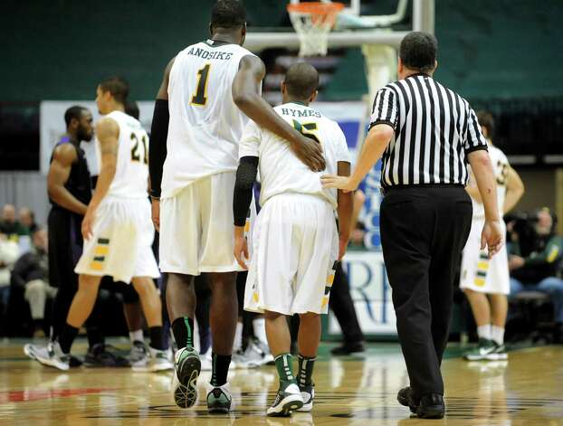 Siena's O.D. Anosike (1), left, and an official, right, assist Evan Hymes (5) to Niagara's free-throw line during their basketball game on Friday, Jan. 25, 2013, at Times Union Center in Albany, N.Y. Hymes was reacting to fouling the opponent in the final seconds. (Cindy Schultz / Times Union) Photo: Cindy Schultz / 00020763A